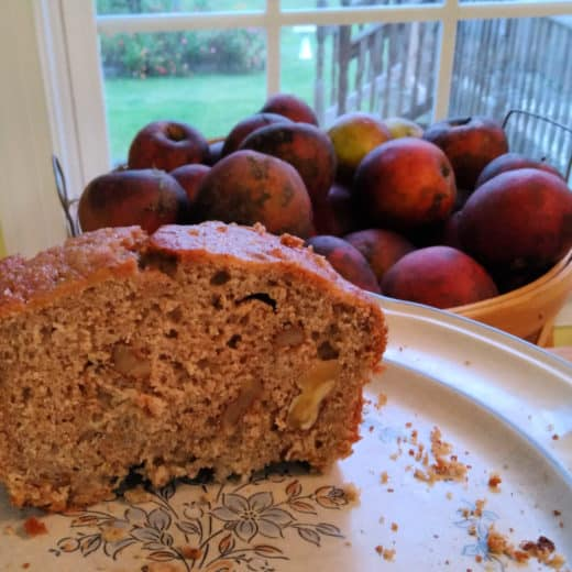 walnut applesauce bread with apples in the background