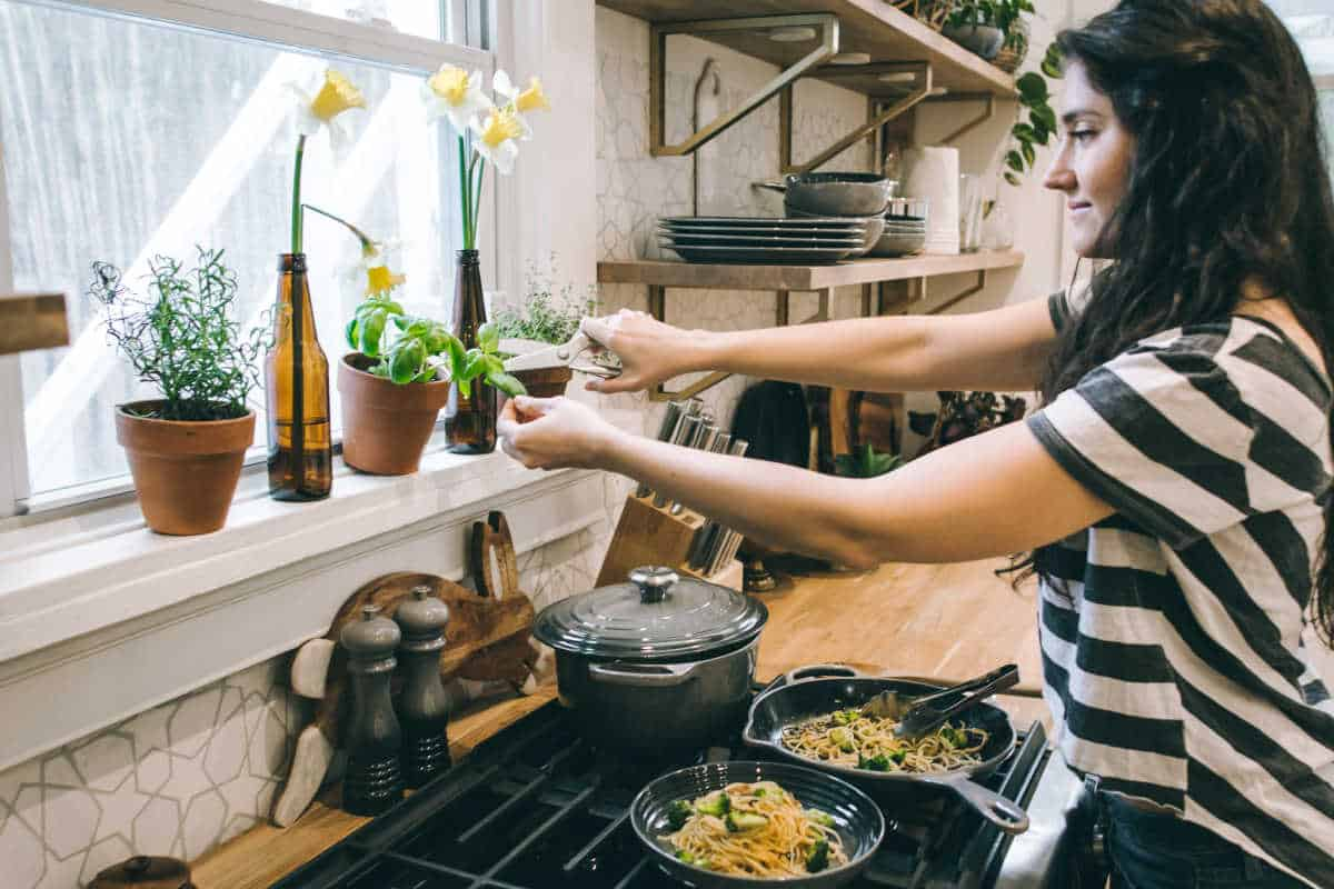 woman cooking and cutting fresh herbs