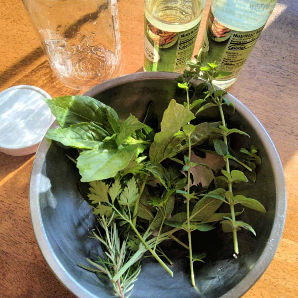 herbs in a metal bowl, glass jar, and wine vinegar