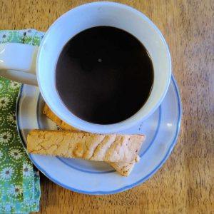 butterscotch biscotti and a cup of black coffee on a plate