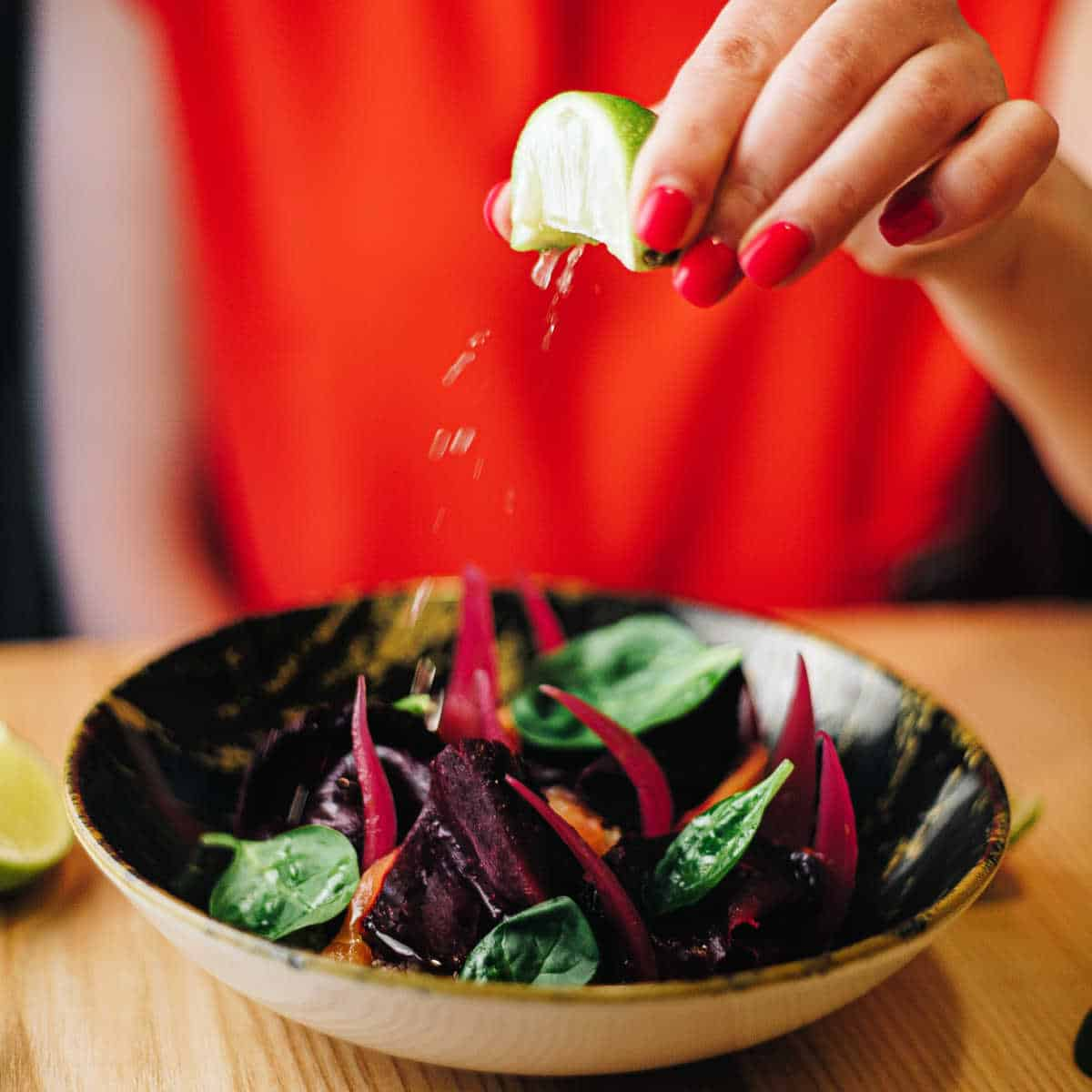 a woman wearing red squeezes a lime over a bowl of spinach salad